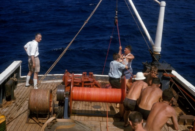 Jacques Cousteau oversees crew as they release anchors and cable.