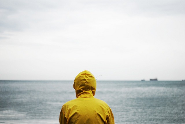 Man in rainjacket looking at ocean