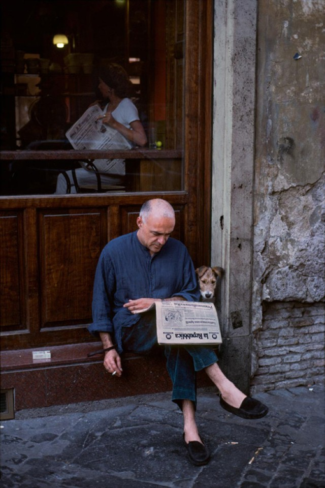 Man reading paper with dog