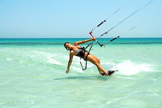 girl kiteboarding in blue water